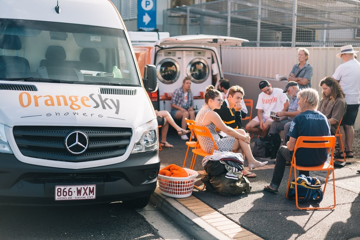Some friends of Orange Sky Australia sitting on a circle of orange chairs in Fortitude Valley chatting