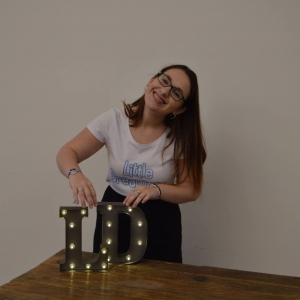 Madeleine standing behind a table smiling. On the table are block letters L and D