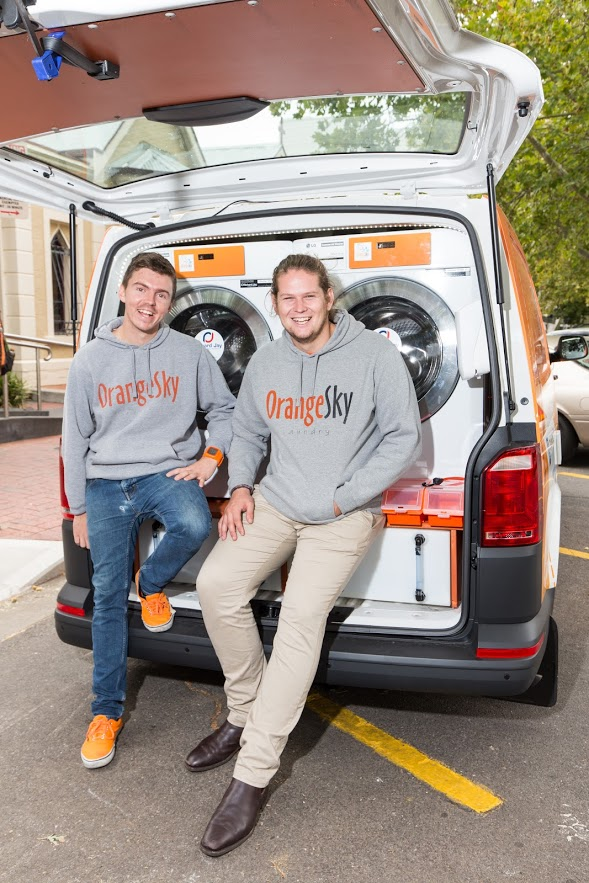 Nic and Lucas of Orange Sky Australia sitting at the bank of the van with the boot open