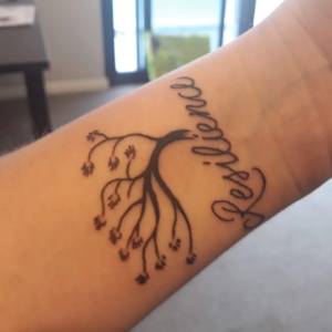Resilience tattooed on my left forearm just below an outline of a tree with gnarled branches.